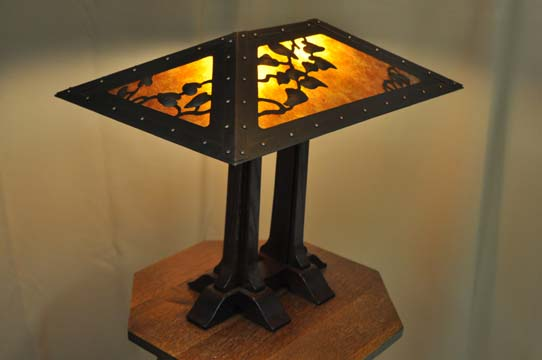 Reproduction Limbert Two Column Table Lamp. Stained quartersawn white oak base with hand hammered copper shade and embossed ivy motif. Amber Mica panels